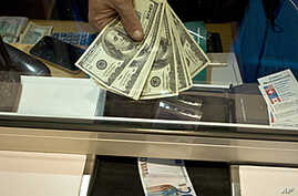 An employee of a currency exchange office displays US dollars next to a 20-euro note on January 6, 2012 in Lyon.