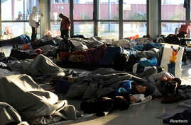 Refugees and migrants sleep inside a passenger terminal at the port of Piraeus, near Athens, Greece, Feb. 7, 2016.