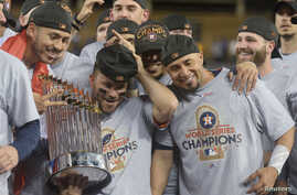 Houston Astros second baseman Jose Altuve celebrates with teammates and the Commissioner's Trophy after defeating the Los Angeles Dodgers in Game 7 of the 2017 World Series at Dodger Stadium, Los Angeles, Nov. 1, 2017. Gary A. Vasquez-USA TODAY Sport