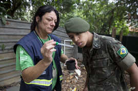 A health agent from Sao Paulo's Public health secretary shows an army soldier Aedes aegypti mosquito larvae that she found during clean up operation against the insect, which is a vector for transmitting the Zika virus, in Sao Paulo, Brazil, Jan. 20,...