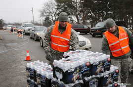 Michigan National Guard members distribute water to a line of residents in their cars in Flint, Michigan, Jan. 21, 2016.