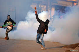 A demonstrator hurls a stone amidst smoke from tear gas fired by Indian policemen during a protest in Kashmir, in Srinagar, Jan. 13, 2018.