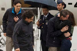 This photo made available by Presidencia del Gobierno on Sunday, May 8, 2016, the three freed Spanish journalists Antonio Pampliega, right, Jose Manuel Lopez, left, and Angel Sastre, arrive at the Torrejon military airbase in Madrid, Spain.
