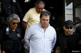 FILE - Former senator Gim Argello is escorted by federal police officers as he leaves the Institute of Forensic Science in Curitiba, Brazil, April 13, 2016.