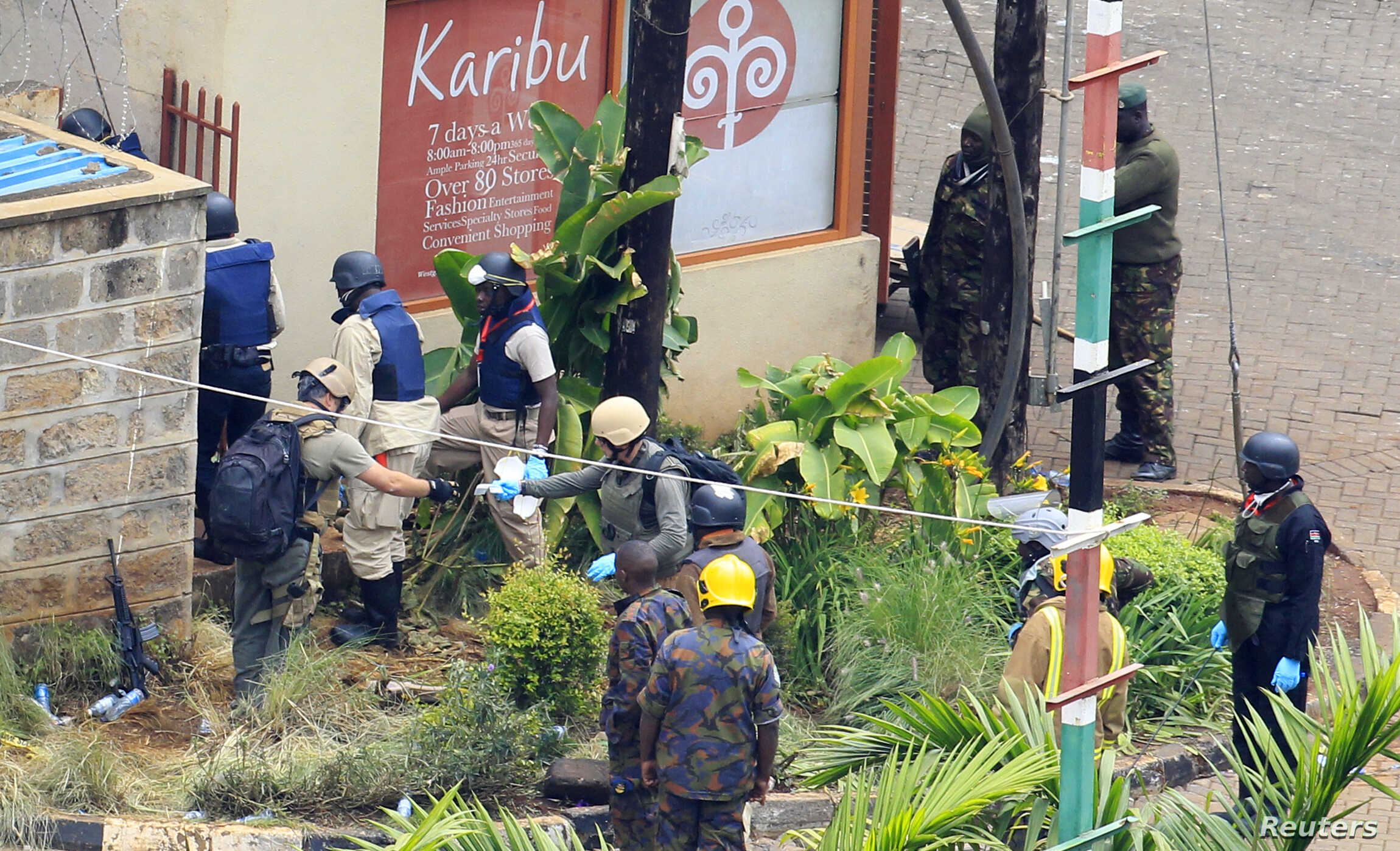 Foreign forensic experts, flanked by Kenyan military personnel, check the perimeter walls around Westgate shopping mall in Nairobi September 25, 2013. Bomb disposal experts and investigators searched through the wreckage of the Kenyan shopping mall o