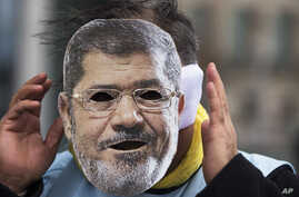 A man covers his face with a mask of Egypt President Mohammed Morsi during a protest in front of the chancellery against the visit of Morsi prior to a meeting of him with German Chancellor Angela Merkel in Berlin, Germany, January 30, 2013.