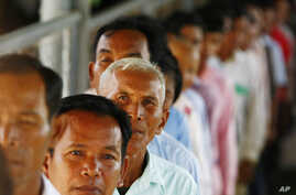 Cambodians line up at a court entrance before a hearing to prepare for the genocide trial of two surviving leaders Khieu Samphan and Noun Chea, at the U.N.-backed war crimes tribunal in Phnom Penh, Cambodia, July 30, 2014.