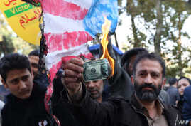A protester burns a dollar banknote during a demonstration outside the former US embassy in the Iranian capital Tehran. Nov. 4, 2018.