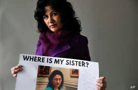 Rushan Abbas, 51, of Herndon, Va., holds a photo of her sister, Gulshan Abbas, Monday, Dec. 17, 2018, in Washington. Rushan Abbas, a Uighur in Washington, D.C., said her sister is among the many Uighurs detained.