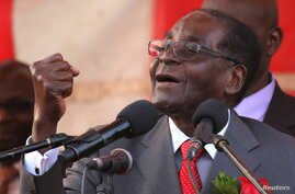 Zimbawe's president, Robert Mugabe, gestures as he addresses supporters of his ruling ZANU-PF party at Harare International Airport, Zimbabwe, Sept. 24, 2016.
