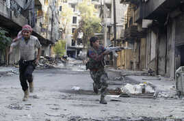 FILE - Mohammad (R), a 13 year-old fighter from the Free Syrian Army, aims his weapon as he runs from snipers loyal to the Syrian regime in Aleppo's Bustan al-Basha district October 29, 2013.