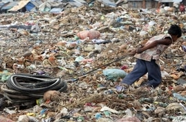 FILE - Young Cambodian boy pulls bicycle tires at Stung Meanchey rubbish dump, Phnom Penh.