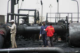 Sudanese workers inspect burnt out oil pipes at the oil-rich border town of Heglig, Sudan, April 24, 2012 (file photo).