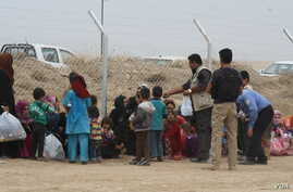Families wait by the fence as soldiers screen incoming refugees in Khazir Camp in the Kurdish region of northern Iraq, Oct. 28, 2016. (H. Murdock/VOA)