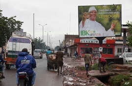 "FILE - Motorbike taxis ride past a giant billboard of Mali's incumbent president, Ibrahim Boubacar Keita, that reads ""the great Mali advance"" in Bamako, Mali, July 18, 2018. As deadly attacks by extremists become more brazen in Mali, officials and ci"