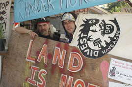 FILE - Black Wolf (L) and Xenoa Skinieth, protesters opposed to the expansion project for an oil pipeline through the Canadian Rockies, stand amid protest signs at the entrance to the Kinder Morgan Inc. oil tank facility on Burnaby Mountain above the