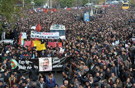 Thousands of people march during the funeral of Tahir Elci, president of the Diyarbakir Bar Association and a leading human rights defender, in Diyarbakir, Turkey, Nov. 29, 2015.