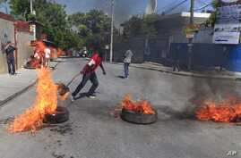 A protester supporter of presidential candidate Moise Jean-Charles, of the Platform Petit Dessalines political party sets fire to a tire during a protest in Port-au-Prince, Haiti, Thursday, Oct. 29, 2015.