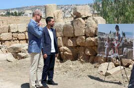 Britain's Prince William and Jordanian Crown Prince Hussein look at a photograph showing William's wife, the former Kate Middleton, her father Michael and younger sister Pippa in the ruins of the Roman city of Jerash in the 1980s in Jerash, Jordan, J