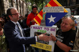 Mayor of Mollerussa Marc Solsona greets a supporter holding a ballot box after testifying at the State Prosecutor's office in Barcelona, Spain, Sept. 19, 2017.