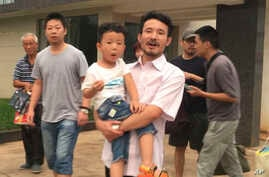 This image taken from video shows Chinese labor activists Hua Haifeng, center, carrying his son, Bobo, and Li Zhao, second from left, leaving a police station after being released in Ganzhou in southern China's Jiangxi province, June 28, 2017. Chines