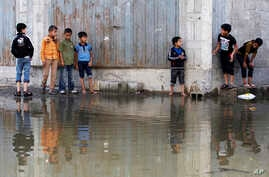 Palestinian children try to cross a waste water - flooded street in Gaza City,  Nov. 14, 2013.