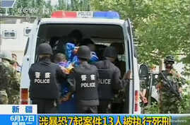 FILE - Riot policemen lead men who are about to be executed into a police van in this still image taken from video in an unknown location in the Xinjiang Uighur Autonomous Region.