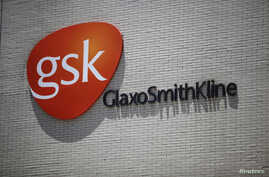 FILE - The logo of GlaxoSmithKline (GSK) is seen on its office building in Shanghai.