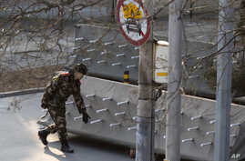 Chinese paramilitary policemen close off a road leading into embassies in the Sanlitun district of Beijing, China, Thursday, Dec. 24, 2015.