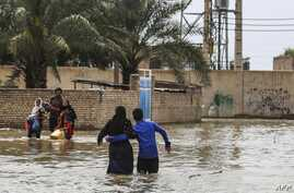An Iranian family walks through a flooded street in a village around the city of Ahvaz, in Iran's Khuzestan province, on March 31, 2019.