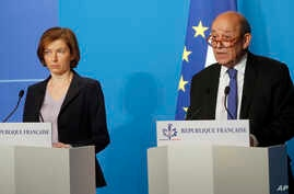 French Minister for Foreign Affairs Jean-Yves Le Drian, right, and French Defense Minister Florence Parly give an official statement in the press room after attending an emergency meeting with French President Emmanuel Macron at the Elysee Palace, in