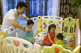 "FILE - Tony Jiang poses with his three children at his house in Shanghai September 16, 2013. In December 2010, Jiang, a Shanghai businessman and his wife welcomed a daughter, born in California to an American surrogate he calls ""my Amanda"". The same"