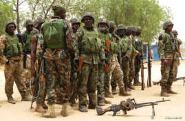 Soldiers stand during a parade in Baga village on the outskirts of Maiduguri, in the north-eastern state of Borno, Nigeria, May 13, 2013.