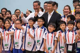China's President Xi Jinping (center right) and Hong Kong's Chief Executive Leung Chun-ying (center left) give thumbs up as they pose for photographs with members of the Hong Kong Police Force's Junior Police Scheme during a visit to a youth camp in