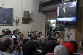 Anti-President Mohamed Morsi protesters watch a speech by him on TV at a cafe in Tahrir Square in Cairo, July 2, 2013.
