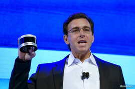Ford Motor Co CEO Mark Fields holds up a new Velodyne LiDAR sensor at the Ford news conference at the Consumer Electronics Show in Las Vegas, Jan. 5, 2016.
