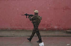 A member of Afghan security personnel arrives at the site of an attack at a military academy in Kabul, Afghanistan, Jan. 29, 2018. Afghan security forces arrested eight militants after members of the Islamic state group attacked a military academy in