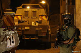 An Israeli soldier stands guard in the West Bank city of Hebron June 15, 2014.