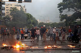 Opposition supporters build a barricade while clashing with riot security forces during a rally against President Nicolas Maduro in Caracas, Venezuela, May 10, 2017.