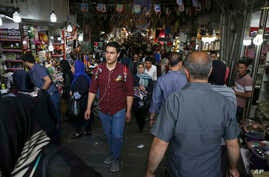 Iranians walk through Tehran's old main bazaar, May 6, 2018. From airplanes to oilfields, billions of dollars are on the line for international corporations as President Donald Trump weighs whether to pull America out of Iran's nuclear deal with worl