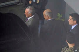 FILE - In this photo shot through a fence, former Brazilian President Michel Temer, left, is seen at the international airport in Sao Paulo, Brazil, March 21, 2019.