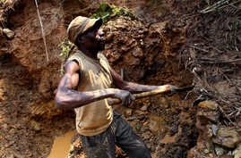 One of few remaining miners digs out soil which will later be filtered for traces of cassiterite, the major ore of tin, at Nyabibwe mine, in eastern Congo, Aug. 7, 2012.