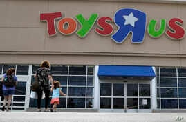 FILE - Shoppers walk into a Toys R Us store, in San Antonio, Texas, Sept. 19, 2017. Toys R Us says it will be closing some U.S. stores and converting others to cobranded locations as it continues to deal with its financial restructuring following its