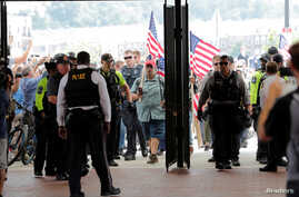 """Police officers await the arrival of Jason Kessler at Vienna Metro Station, on the one year anniversary of the 2017 Charlottesville """"Unite the Right"""" protests, in Vienna, Virginia, U.S., August 12, 2018.     REUTERS/Lucas Jackson"""