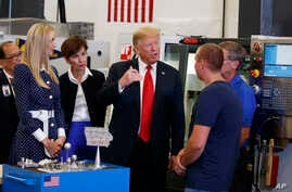 President Donald Trump participates in a tour of an advanced manufacturing lab with Ivanka Trump, second from left, and Gov. Kim Reynolds, R-Iowa, third from left, at Northeast Iowa Community College,  July 26, 2018, in Peosta, Iowa.
