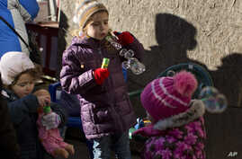 FILE - The children of internally displaced Ukrainian people who abandoned their homes in Donetsk play with donated toys during a food distribution drive in central Kiev, Oct. 25, 2014.
