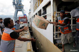 Aid for earthquake and tusnami victims is unloaded from a ship in Palu, Central Sulawesi, Indonesia, Oct. 9, 2018.