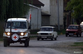 A Red Cross vehicle leads a convoy of paramilitary cars passing throughShemshovo village September 19, 2001 as they withdraw at dusk togetherwith Macedonian security forces from Rataje village, near Tetovo. NATOaccused Macedonian security forces of p