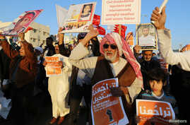 "FILE - An anti-government protester holds a sign reading ""It Is Impossible For The Bahraini People To Give up On Democracy"" as he shouts anti-government slogans during a rally in the village of Bilad al-Qadeem south of Manama, Feb. 11, 2014."