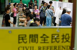 People vote at a polling center for an unofficial referendum on democratic reform in Hong Kong Sunday, June 22, 2014.